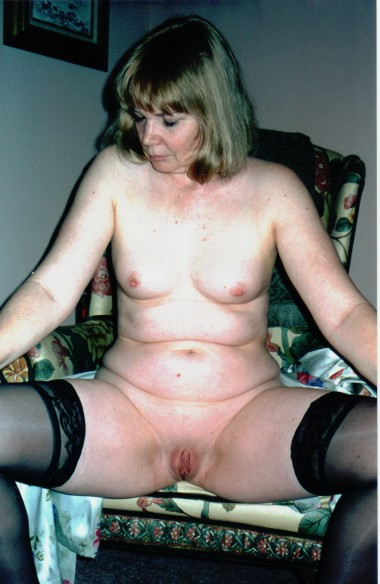 Nude sitting on the chair with exposed breasts and totally shaved pussy